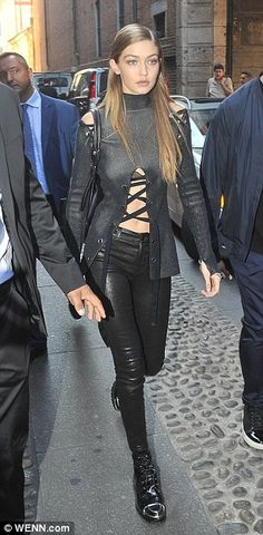 Cheeky: Gigi flashed her taut and toned tum in an unusual high-neck top, which cut out and laced up saucily from the breast down