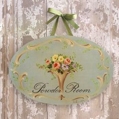 "This plaque features a lovely grey blue background with an urn of gorgeous flowers. The words ""Powder Room"" adorn the middle. It is framed with lovely french scrolls and leaves. Makes a wonderful gift or addition to your restroom! <BR><BR> This oval plaque features a lovely print of a handpainted image affixed to a wooden board.  <BR><BR> • Wood<BR> • Grey Blue<BR> • 10""H x 15""W<BR>  <BR><BR> These items are handmade and may take up to 2-3 weeks before delivery."