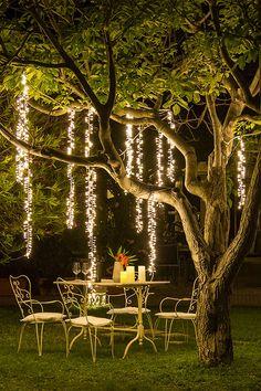 4 Decoration ideas for a romantic evening- 4 Idee di decorazione per una serata romantica Romantic dinner outdoors under a plant illuminated by festoons and cascades of decorative lights -