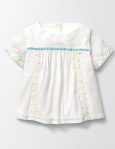We've sewn a daisy chain into this pretty floral top. It's extra floaty thanks to gatherings at the front and back, and perfect for running, jumping and playing. We've finished it off with a bobble trim too (just for fun).