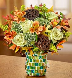 Amber Waves™: fresh green roses and orange alstroemeria, bringing in dried oak leaves and unique lotus pods for a rustic nod to the rolling plains. Set in a charming #mosaic planter.