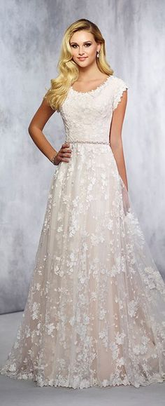 Lace over tulle and chiffon soft A-line gown with scalloped lace cap sleeves, scalloped scooped neckline, covered buttons along the back, lace hem with chapel length train. Shown with BELT11731, sold separately.