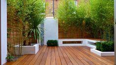 terrasse en bois composite moderne avec une clôture bois et une végétation opulente