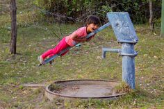 The sheer joy on this little girl's face is what every parent hopes to see their child as. Gay abandon as she hangs mischeviously off a handpump in rural India Small Caps, Rural India, History Of India, Indian People, Girl Face, Royalty Free Photos, Dream Big, Desi, Gay
