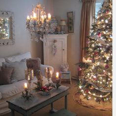 Such a gorgeous room. From the vintage ornaments, white slip cover and incredible yet unexpected chandelier to the cozy candlelight and the distressed table ~ everything in this room works for me...