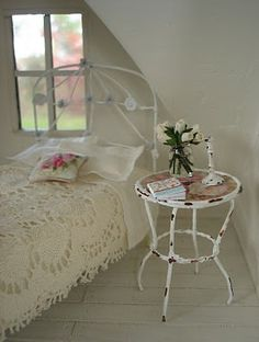 Beautiful iron bed frame and bedside stand, painted wide board wood floors. Cute bedroom in an attic space. Grand kids or guests?