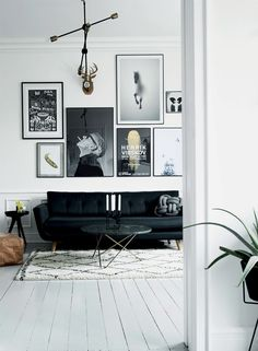 The living room in black and white is made cozier with the help of a cool rug and pillow