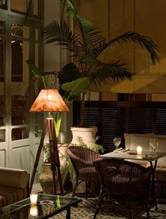 British Colonial style under the warm glow of the lamp.- love this look, reminds me of Hemmingway and Key West!  Good for the living room!