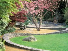 A curving stone wall unites the patio, lawn and planted areas of this landscape design.Home Garden Television Building A Stone Wall, Landscape Design, Garden Design, Family Garden, Garden Cottage, Garden Bed, Garden Pictures, Colorful Garden, Walled Garden