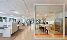 Williams-Sonoma Office // simply gorgeous: hardwood floors, glass wall separators, stainless steel kitchen, and white cubicles with just enough privacy