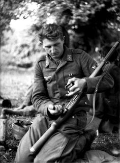 A German Wehrmacht Fallschirmjäger (paratrooper) Obergefreiter (Senior Lance-Corporal) cleans his Karabiner 98 Kurz bolt action rifle in the hedgerows of Normandy following the Allied Landings. Saint-Lô, Manche, Lower Normandy, France. June 1944.