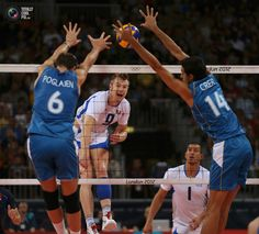 Italy's Ivan Zaytsev spikes the ball against Argentina's Cristian Poglajen and Pablo Crer as Italy's Luigi Mastrangelo looks on during their men's Group A volleyball match at the London 2012 Olympic Games at Earls Court. IVAN ALVARADO/REUTERS