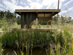 6 Tiny Outdoor Pavilions Inspired by Japanese Tearooms - Photo 1 of 12 - Named after its charred-larch cladding, this tearoom designed by Czech studio A1 Architects sits next to a lake in a wooded area near Česká Lípa, Czech Republic. Its sliding doors can be opened for enhanced connectivity with the surrounding nature, or closed to create a more secluded oasis. At the center of the space is a hearth that has a teapot suspended from the sisal rope-domed ceiling above it.