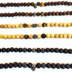 Chaque bracelet est composé de 22 perles de bois noir, beige ou marron, deux pierres (oeil de tigre ou hematite) et d'une perle ou tete de mort en acier inoxydable.  Fermoir en acier reglable par mousqueton.