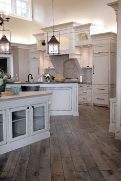 Distressed and stained gray, vintage hardwood floors. Gorgeous kitchen lighting and cabinetry.