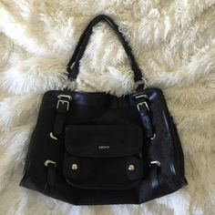 "DKNY Black Handbag Town and Country Pocket handbag. Top clasp closure,with big pocket on the outside. Lots of compartment inside. DKNY printed all over. Can be a shoulder bag. Price firm. Measures approx. W13"" H8"" D 4"" and strap drop of 9"" DKNY Bags"