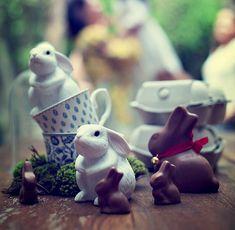 Xícaras empilhadas e bichinhos de porcelana e chocolate decoram a mesa das lembrancinhas, guardadas em caixas de ovos