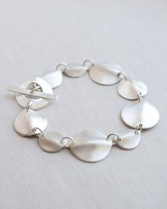 Rippled Disk Bracelet by Olive Yew. This beautifully handmade rippled disk bracelet in surprisingly lightweight and streamlined. These wavy disks alternate in size between 1/2 inch in diameter and 3/4 in diameter.