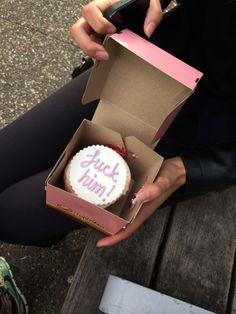 """She handed her a bubble gum pink cardboard card box. She opened it and inside was a small cake with a white card on top and in pink the words """"fuck him!"""" She gasped and looked at her best friend, who smirked and nodding. """"Well I guess that settles it"""" she got up, taking the cake from her friend."""