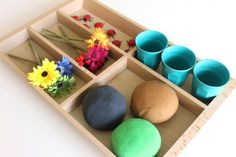 A shallow wooden tray set out with play dough, faux flowers, plastic ladybugs and three small plastic pots.