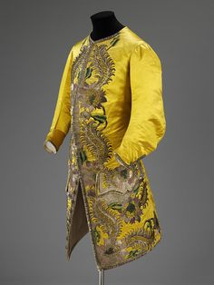 Satin dyed, a brilliant sunshine hue forms the body of this court waistcoat of the 1730s. Such a rich yellow was fashionable in men's and women's dress from the 1730s until the 1780s. In keeping with the lavishness of court dress, the waistcoat is embellished with embroidery in coloured silk and silver threads of several textures. A pattern of large flowers and leaves with feathered scrolls cover the front edges, the pocket flaps and the front of the waistcoat skirts. The scale of the…