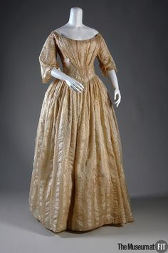 """Dress: ca. 1845, American, striped silk, net. """"The ideal woman of the 1840s was generally plump, but had a slim waistline. Dressmaking techniques could help create an illusion of the perfect figure—in the bodice of this dress, the vertically striped fabric is gathered into a pronounced 'V' shape that lengthens the waist, thus making it appear narrower."""""""