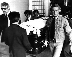 Steve McQueen and James Coburn serve as pallbearers at Bruce Lee's funeral in 1973. Description from funnyjunk.com. I searched for this on bing.com/images