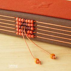 Longstitch binding decorated with glass beads / Encuadernación de puntada larga decorada con cuentas