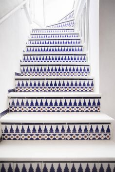 patterned blue tiles on staircase. mexican influenced, spanish, moorish architecture with patterned tiles.