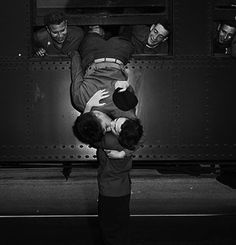 A soldier hangs out of a train to kiss his girl.   19 Kisses Captured At The Perfect Moment