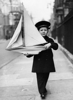 Boy with Toy Sailboat Wearing Peacoat and Sailor Hat.