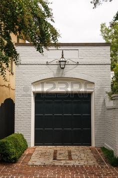 An old white brick free standing garage with a black wood door beyond a brick driveway