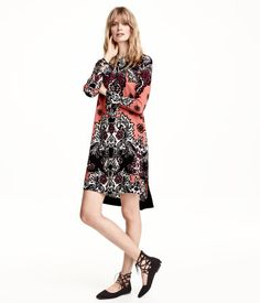 Long-sleeved, straight-cut dress in lightly creped, woven fabric with a printed pattern. Covered buttons at back, slit with button and flounce at cuffs, and slits at sides. Unlined.