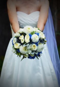 White dahlias, blue hydrangea, spray roses, and blue thistle were used to create this bridal bouquet. Photography by Saskia.