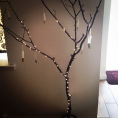 Alternative christmas tree. Large branch in a glass pot, secured with flower foam and plaster of Paris. Branch spray painted with silver and finished with silver glitter glue on the small branches. Feathers with glitter tips to finish