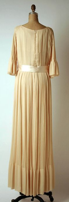 Christian Dior evening dress Haute Couture by designer Marc Bohan from spring summer 1972. Pleat and pleated long maxi gown made from ivory color silk with ribbon tied at the waist. House of Dior.