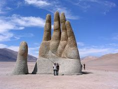 """La Mano del Desierto, meaning """"Hand of the Desert,"""" is a giant hand merging out of the ground in the Atacama Desert in Chile. This stone hand is about 36 feet tall and has a base made of iron and cement. The Atacama Desert is the driest desert in the world (bet you didn't know that!). The sculpture was finished in 1992 by the Chilean artist Mario Irarrazabal, which was meant to symbolize the emphasis on human vulnerability and helplessness."""