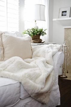 all-white room with comfy throw, alabaster lamp with linen shade, fresh green plant.....perfect.