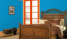 This blue room is complemented by red-orange and yellow-orange, creating a split complementary color scheme. The neutral furniture and bedding go well with any color scheme, and can tone down the bright colors in this split complementary color scheme.