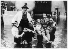 """Director Fritz Lang and cinematographer Karl Freund being carried through the flooded Worker's City on the set of """"Metropolis"""", 1927"""
