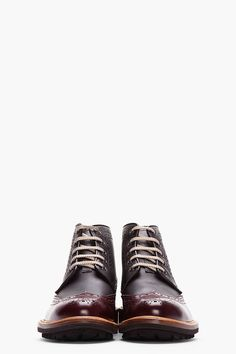 DSQUARED2 //  Black & Burgundy Leather Othello Brogue Boots  32148M047003  High tiop leather wingtip brogue boots in black. Round toe. Grey lace up closure with gunmetal tone eyelets. Signature perforated detail and serrated edges throughout. Contrast polished leather panels in burgundy at toe and heel. Tan welt. Brown foxing. Tone on tone stitching. Leather upper, rubber sole. Made in Italy.  $740 CAD