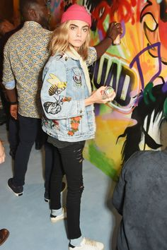 August 4, 2016 In a Gucci patchwork denim jacket, pink beanie, black distressed jeans, dotted light blue socks and white sneakers at the Meades mural in London