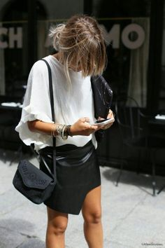 Slouchy white shirt, black leather skirt and messy hair. Minimalist style.