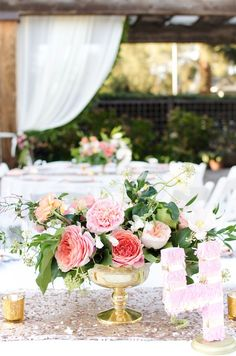 Lovely peach and pink florals, arranged in a classic gold urn. | by Gavita Flora #coral #wedding #flowers