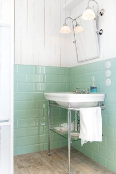 Watery green tile and whitewashed shiplap cover the walls in a bathroom in the main house. | From Sweden with Love: A Romantic Captain's Seaside Villa