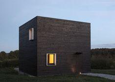 Van een afstand lijkt het een verbrande schuur, maar het is eigenlijk een vierkant huis opgebouwd met zwart geverfd hout. Het huis is gelegen in Normandië, Frankrijk en gemaakt door Parijs studio B...