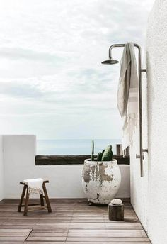 Outdoor shower: Rinsing off after a swim is a stylish affair with Anatolian Turkish towels and a tall outdoor shower. Cacti thrive in a rustic planter from The Pot Warehouse. Stool, Orient House