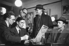 A group of men examine a work by English painter, war artist, occultist and joint editor of the 'Golden Hind' art quarterly, Austin Osman Spare (1886 - 1956, second from right), London, 1953. Original Publication: Picture Post 6627 - Austin Osman Spare - unpub - 1953