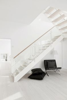 A white modern hall with white stairs and the Barcelona Chair of Ludwig Mies van der Rohe that gives a sleek interoir style. Interior Architecture, Interior And Exterior, Interior Design, Interior Styling, Glass Stairs, Glass Railing, White Stairs, Beautiful Stairs, Black And White Interior
