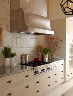 stainless steel counters on white lowers, great large-format tile on the wall w/geometric cage pendant